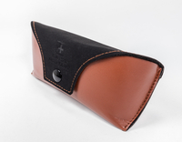 A Brown And Black Eyeglass Case with A LOGO Printed on It Looks Like A Leather Wallet
